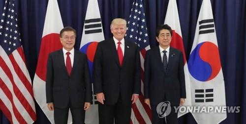 当地时间7月6日下午,在德国汉堡美领馆,韩国总统文在寅(左)、美国总统特朗普和日本首相安倍晋三在共进晚餐前合影留念。(韩联社)