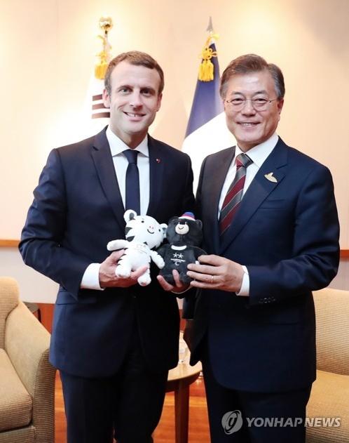 当地时间7月8日下午,在德国汉堡国际会展中心,韩国总统文在寅(右)向法国总统马克龙赠送2018年平昌冬奥会吉祥物。(韩联社)