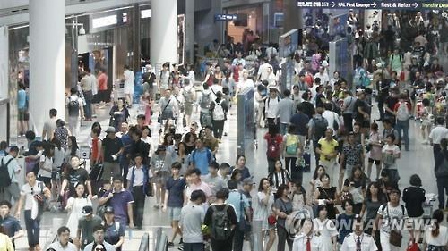资料图片:仁川国际机场出境大厅人头攒动。(韩联社)