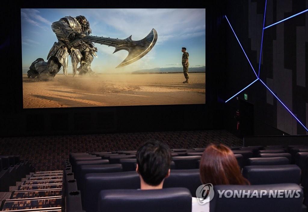 三星电子的广告模特们在观看LED大屏幕电影。(韩联社)