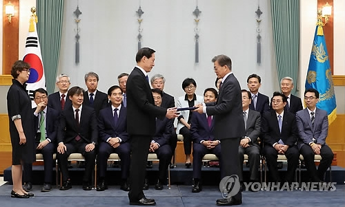 7月13日下午,在青瓦台,总统文在寅(右)向国防部长官宋永武颁发任命书。(韩联社)