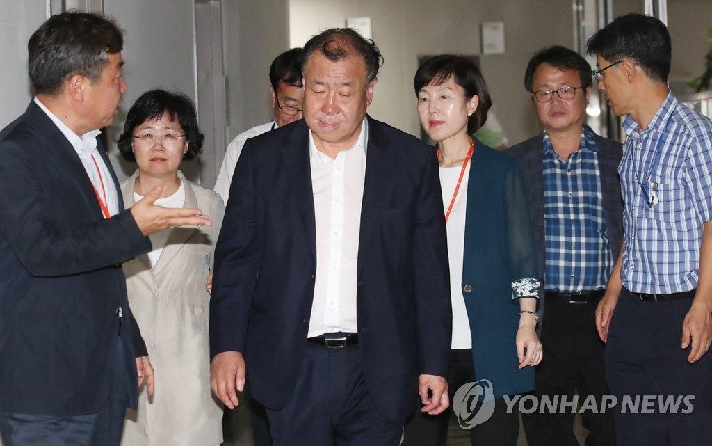 7月15日,在世宗市的韩国中央政府办公楼,最低工资委员会主席鱼秀凤(居中)及公益委员们走入会场。(韩联社)