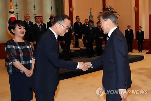 7月25日下午,在青瓦台,文在寅颁发检察总长任命书前与文武一握手。(完)