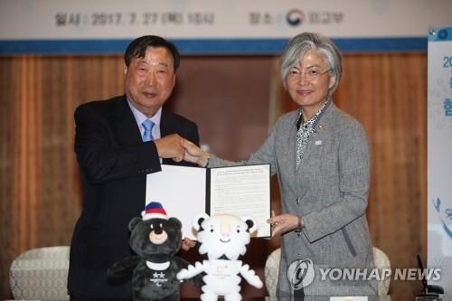7月27日,在首尔韩国外交部大楼,外长康京和(右)与平昌冬奥会组委会主席李熙范签署协议后握手合影。(韩联社)