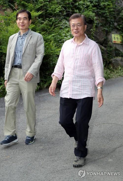 资料图片:5月21日下午抵达位于庆尚南道梁山市的私邸准备度假的韩总统文在寅(右)与总统警卫室长朱英训(韩联社)