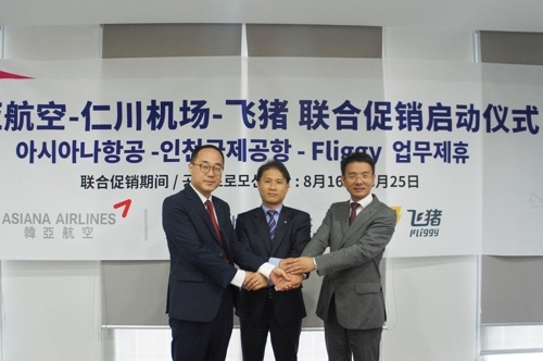 8月2日,在北京,飞猪国际机票平台商务合作总经理汤文开(右一)与韩亚航空及仁川机场代表手牵手启动联合促销活动。(韩联社/韩亚航空提供)
