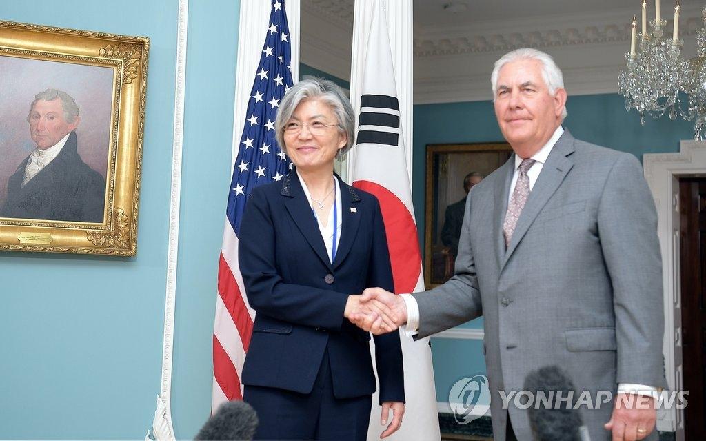 资料图片:当地时间6月28日,在华盛顿,韩国外交部长官康京和(左)和美国国务卿蒂勒森亲切握手合影。(韩联社/韩国外交部提供)