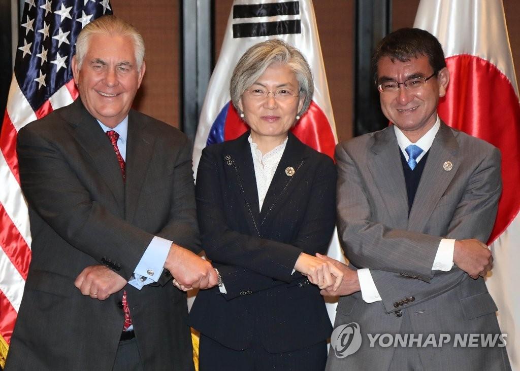 8月7日,在马尼拉市区某酒店,韩国外交部长官康京和(左二)、美国国务卿蒂勒森(左一)、日本新任外务大臣河野太郎举行会谈。图为三方握手合影留念。(韩联社)