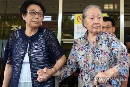 8月11日下午,日本殖民时期被强征劳役的两位受害人胜诉后走出法院。(韩联社)