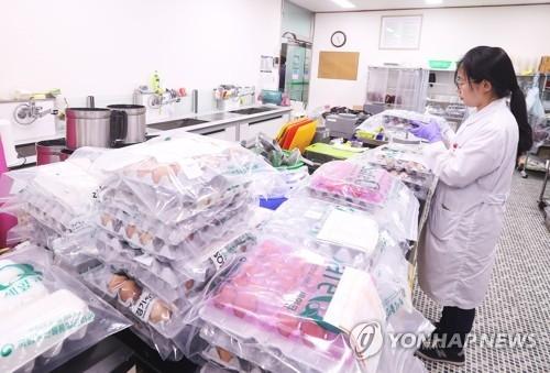 资料图片:8月16日,在京畿道国立农产品品质管理院京畿分院,工作人员在检查鸡蛋。(韩联社)