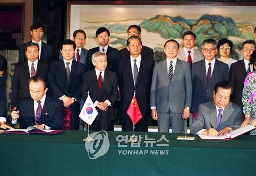 资料图片:1992年8月24日,在北京,时任韩国外长李相玉(左)和时任中国外长钱其琛在韩中建交联合公报上签字。(韩联社)