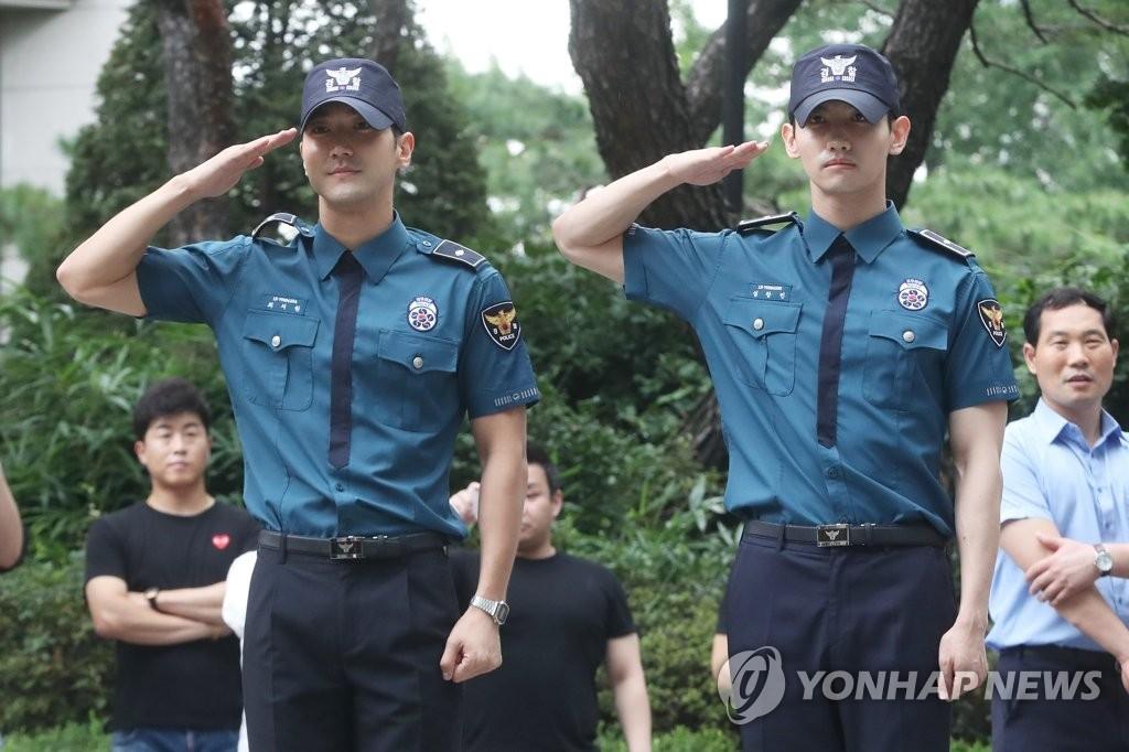 8月18日上午,在首尔地方警察厅,Super Junior崔始源(左)和东方神起最强昌珉正式退伍。(韩联社)
