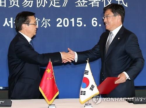 资料图片:2015年6月9日,韩国产业通商资源部长官尹相直(右)和中国商务部长高虎城签订韩中自贸协定后握手。(韩联社)