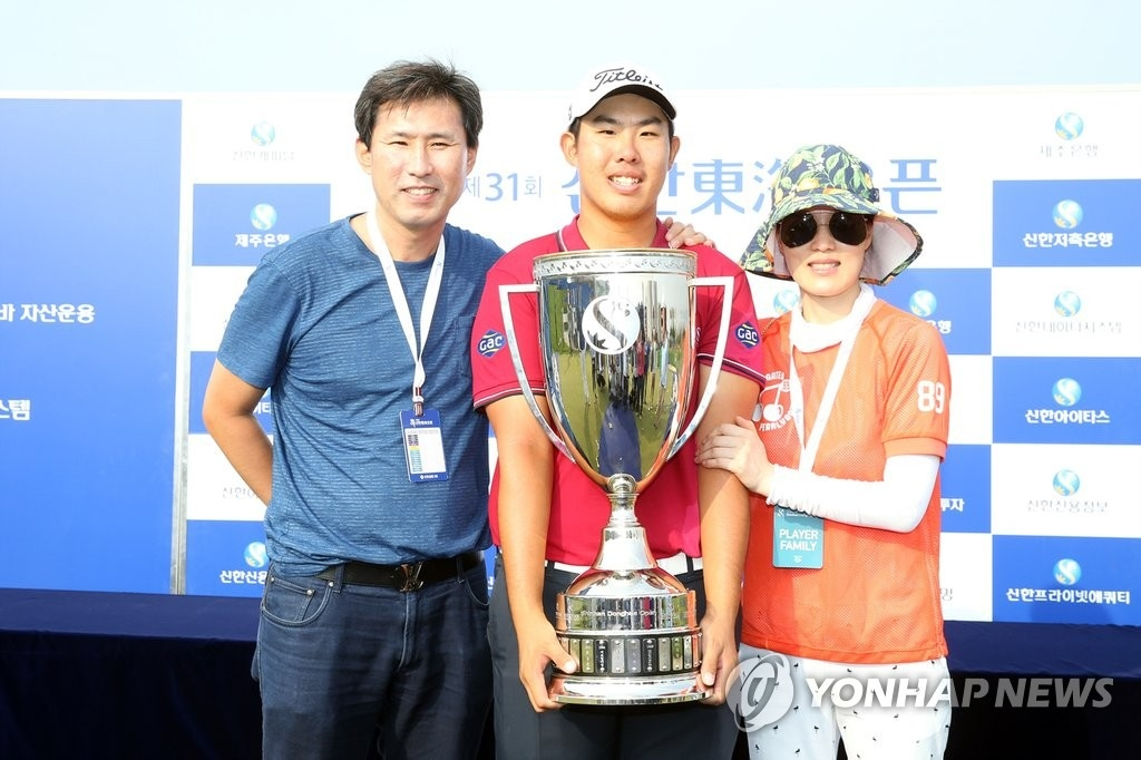 资料图片:2015年9月20日,在韩国职业高尔夫巡回赛(KGT)第31届新韩东海公开赛上,安秉勋捧着冠军奖杯和父母合影。(韩联社)