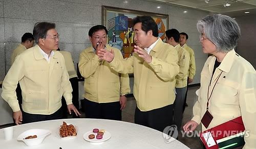 8月23日,在韩国外交部大楼,总统文在寅(左一)与国务总理李洛渊(右二)、外长康京和(右一)交谈。(韩联社)