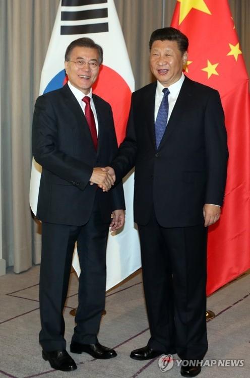当地时间7月6日上午,在德国柏林,韩国总统文在寅(左)和中国国家主席习近平会晤,双方亲切握手。(韩联社)