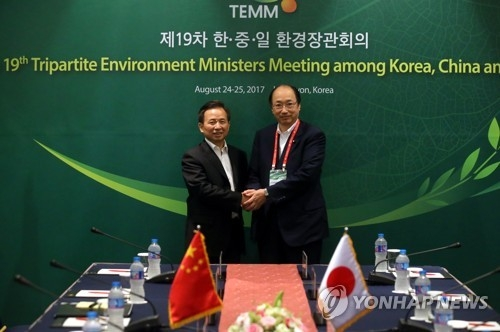8月24日下午,在韩国京畿道水原市,中国环保部长李干杰(左)与日本环境大臣中川正春在双边会谈上握手。(完)