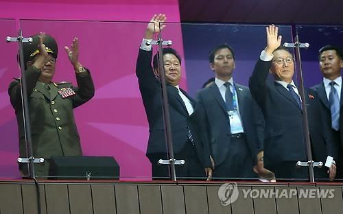 资料图片:2014年10月,在仁川亚运会闭幕式上,朝鲜高层官员出席并挥手致意,左起依次是黄炳誓、崔龙海、金养健。(韩联社)