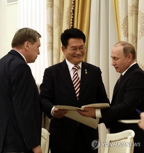 资料图片:5月24日,在莫斯科的克林姆林宫,访俄特使宋永吉(中)向俄罗斯总统普京转交韩国总统文在寅的亲笔信。(韩联社)