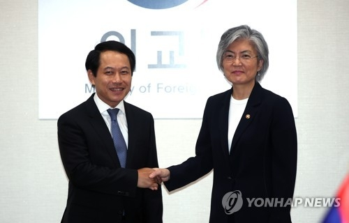 8月29日上午,在外交部大楼,韩国外长康京和(右)与老挝外交部部长沙伦赛·贡玛西举行会谈前握手。(韩联社)