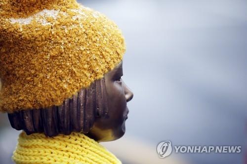 资料图片:12月26日,位于首尔市钟路区的日本驻韩大使馆对面,日军慰安妇少女铜像凝视着前方。28日,韩日外长将为解决慰安妇问题在首尔举行会谈。韩联社