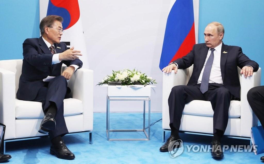 资料图片:当地时间7月7日下午,在德国汉堡国际会展中心,韩国总统文在寅(左)与俄罗斯总统普京举行会谈。(韩联社)