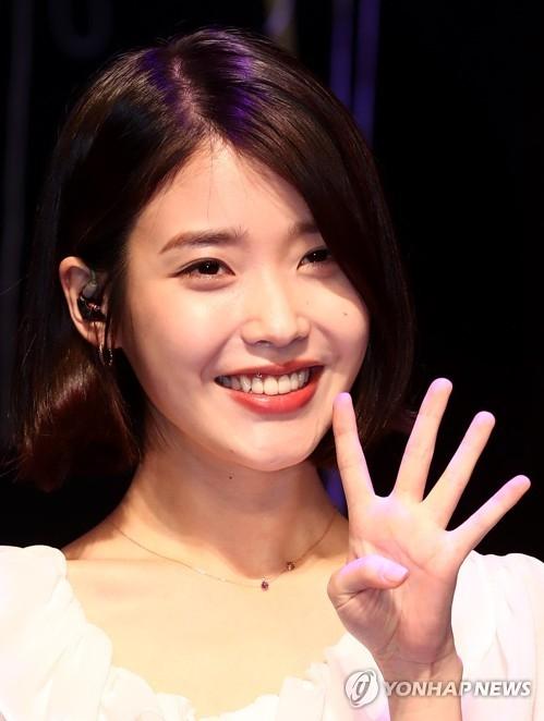 资料图片:4月21日下午,在首尔麻浦区新韩卡Fan Square,歌手IU在第四张迷你专辑《Palette》试听会上接受媒体拍照。(韩联社)