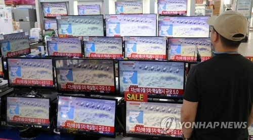 9月3日,在一家电卖场,一名市民在收看朝鲜地震的新闻报道。(韩联社)