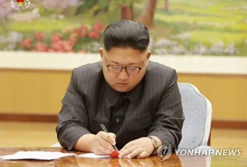 朝鲜中央电视台9月3日播出的画面中,金正恩似在洲际弹道导弹氢弹头试验命令书上签字。图片仅限韩国国内使用,严禁转载复制。(韩联社/朝鲜中央电视台)