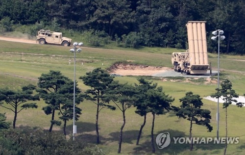 9月4日下午,在庆尚北道星州郡,美军车辆驶过萨德发射车附近。(韩联社)