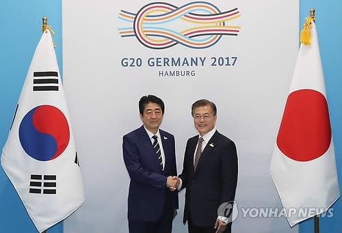 资料图片:当地时间7月7日,在德国汉堡,韩国总统文在寅(右)和日本首相安倍晋三在首脑会谈上亲切握手。韩联社 (END)