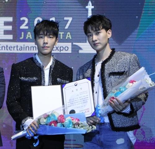 9月4日晚,在印尼雅加达韩流博览会上,东海(左)和银赫获得韩国产业通商资源部长官表彰证书。(韩联社/大韩贸易投资振兴公社提供)
