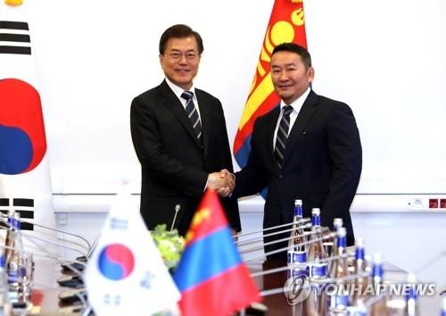 当地时间9月6日下午,在俄罗斯符拉迪沃斯托克远东联邦大学,韩国总统文在寅(左)与蒙古国总统哈勒特马·巴特图勒嘎在会谈前握手合影。(韩联社)