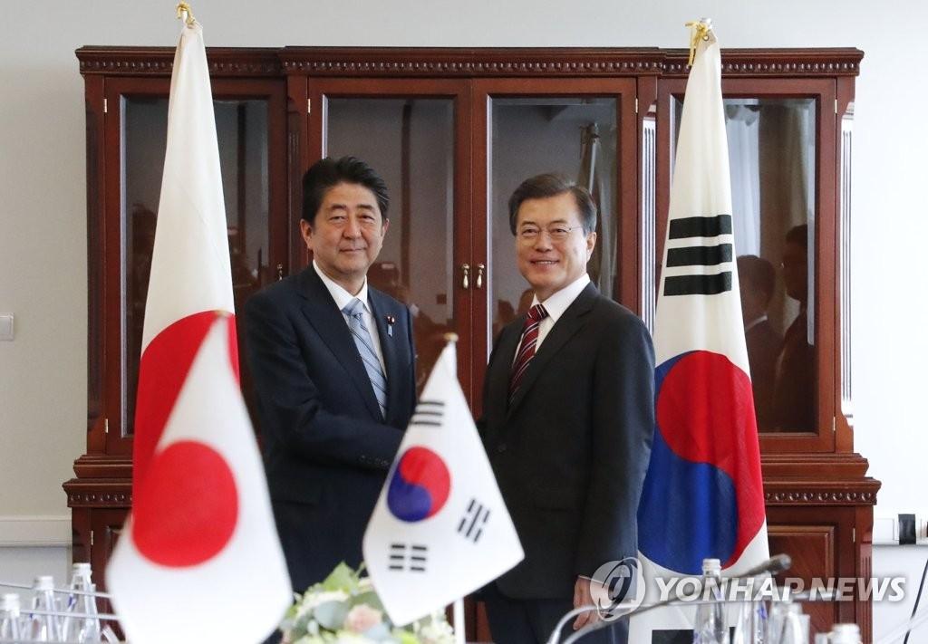 9月7日,在俄罗斯符拉迪沃斯托克远东联邦大学,韩国总统文在寅(右)和日本首相安倍晋三举行会谈时握手。(韩联社)