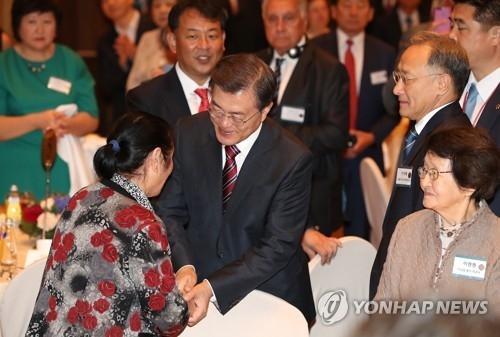 9月7日,在俄罗斯符拉迪沃斯托克现代酒店,出席旅俄韩人韩侨座谈会的韩国总统文在寅与被强征至库页岛的第一代韩人代表握手。(韩联社)