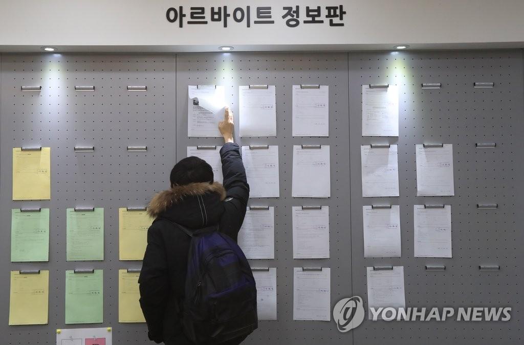 资料图片:2017年3月份,在首尔建国大学,一名学生在查看打工招聘公告。(韩联社)