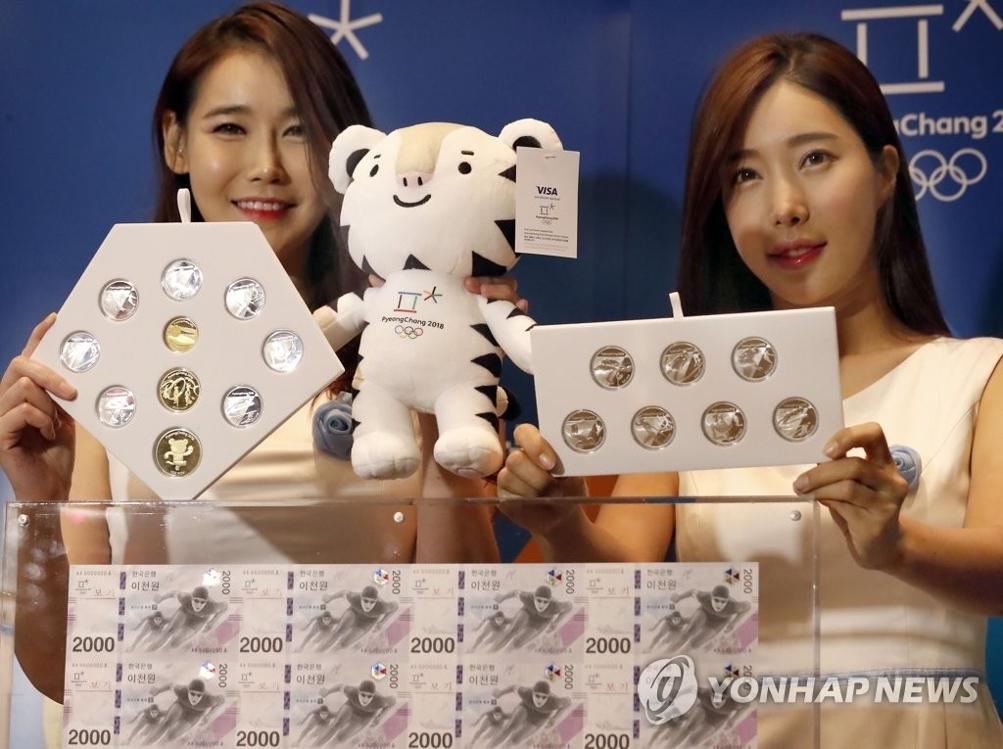 资料图片:9月1日上午,2018平昌冬奥会纪念钞和纪念币公开活动在首尔举行,工作人员展示纪念钞与纪念币。(韩联社)