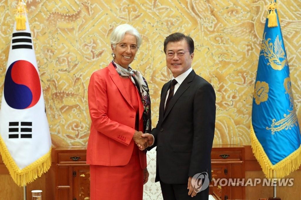 11日上午,在韩国总统府青瓦台,总统文在寅(右)与国际货币基金组织总裁克里斯蒂娜•拉加德握手。(韩联社)