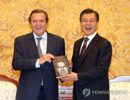 9月12日下午,在青瓦台,德国前总理施罗德(左)向韩国总统文在寅赠送其自传韩语版本。(完)