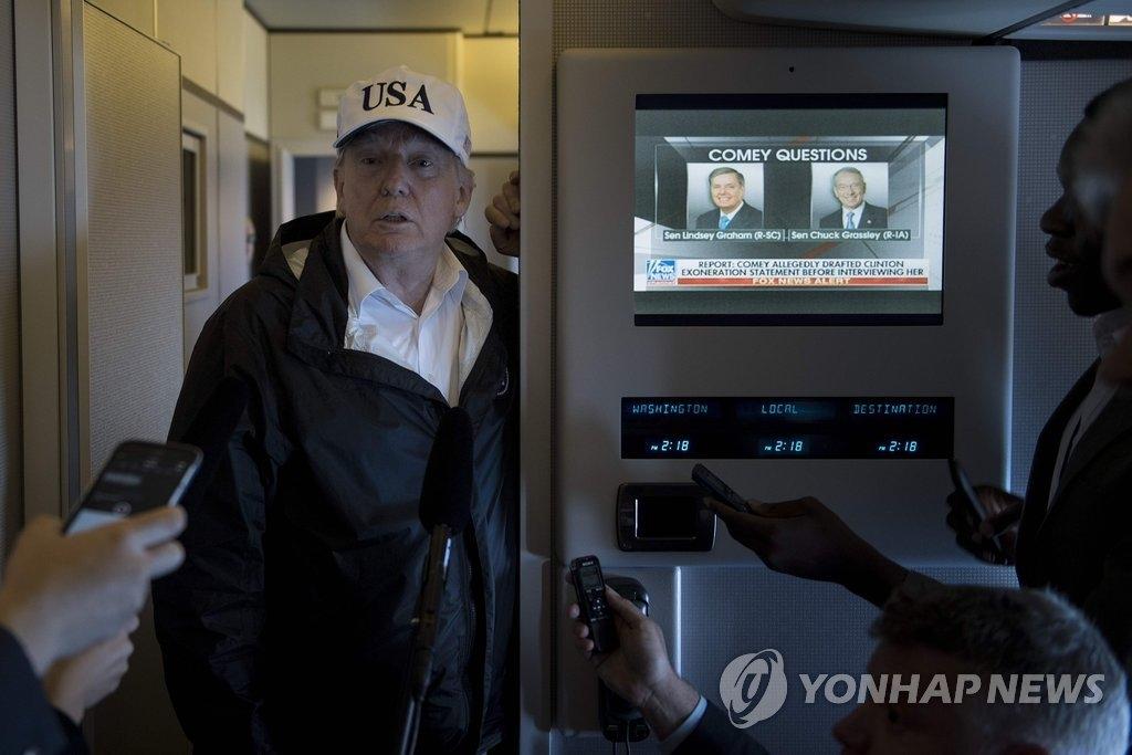特朗普在机上答记者问。(韩联社/法新社)