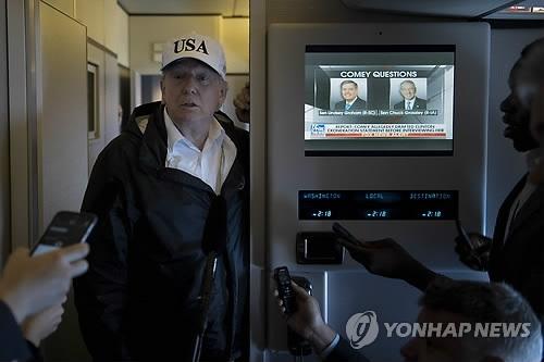 """当地时间14日,在""""空军一号""""总统专机上,特朗普答记者问。(韩联社/法新社)"""