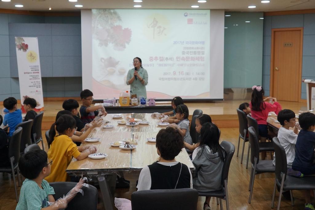 """9月16日,在韩国国立儿童青少年图书馆,首尔中国文化中心和韩国国立儿童青少年图书馆共同主办""""我们的节日——传统文化体验活动""""。图为工作人员现场讲解。(韩联社/首尔中国文化中心提供)"""