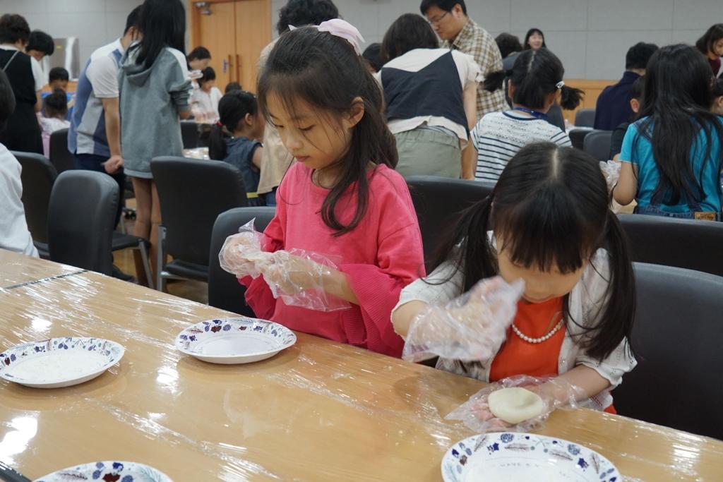"""9月16日,在韩国国立儿童青少年图书馆,首尔中国文化中心和韩国国立儿童青少年图书馆共同主办""""我们的节日——传统文化体验活动""""。图为小朋友们体验制作月饼。(韩联社/首尔中国文化中心提供)"""