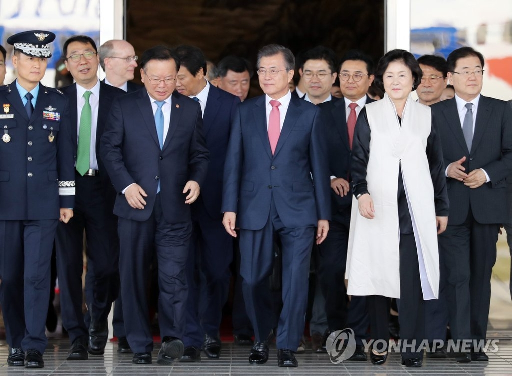 9月18日下午,在城南首尔机场,韩国总统文在寅和夫人金正淑(右二)登机赴美国纽约前,与韩国行政自治部长官金富谦(前排左二)对话。(韩联社)