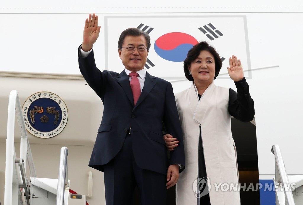 当地时间9月18日,在纽约JFK机场,韩国总统文在寅(左)和第一夫人金正淑女士向迎接人群挥手致意。(韩联社)