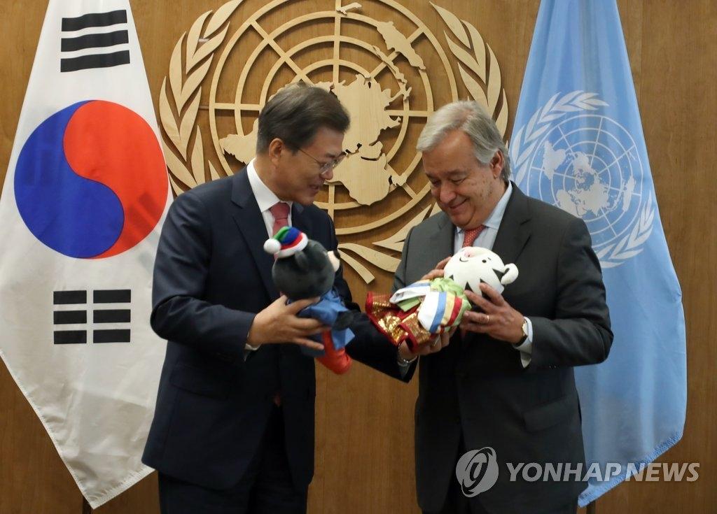 """当地时间9月18日,在纽约联合国总部办公室,韩国总统文在寅(左)向联合国秘书长古特雷斯赠送平昌冬奥会吉祥物""""Soohorang""""和平昌冬残奥会吉祥物""""Bandabi""""。(韩联社)"""