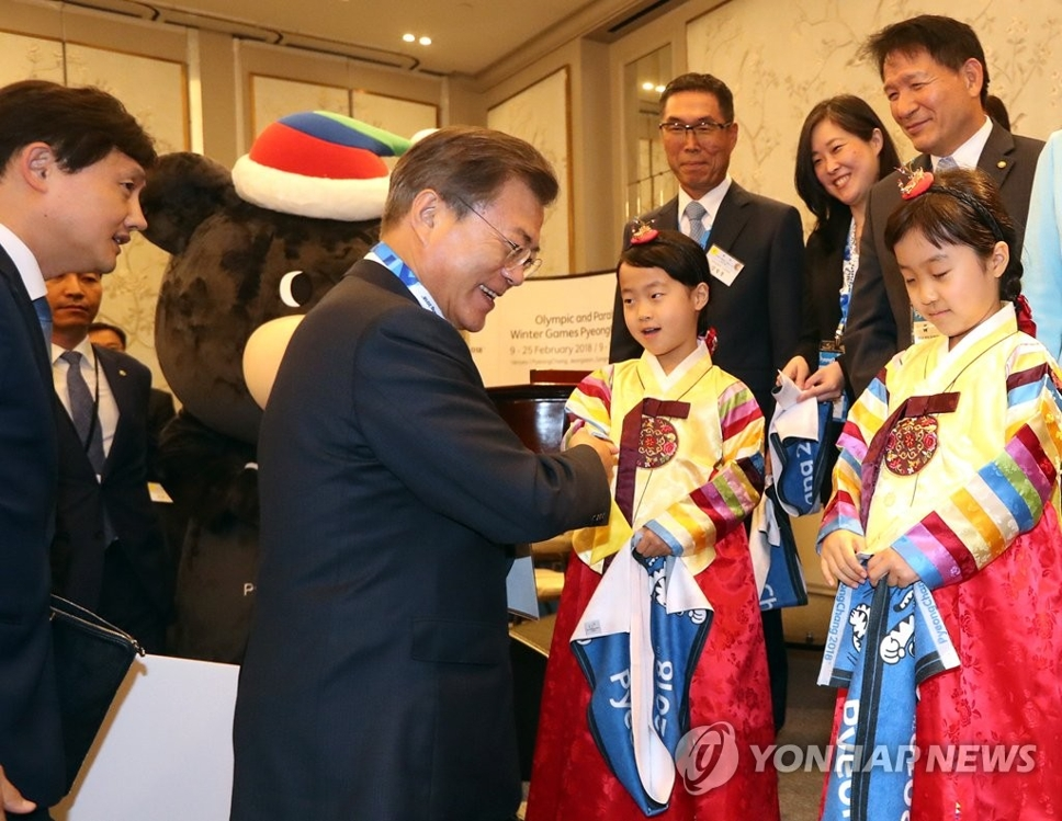 当地时间9月18日下午,在美国纽约洲际大酒店,出席侨团代表座谈会的韩国总统文在寅与身穿韩服的小朋友握手。(韩联社)
