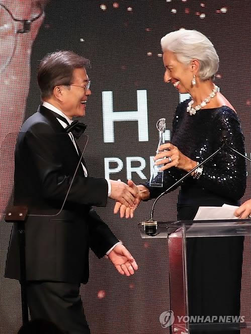"""当地时间9月19日下午,在美国纽约,韩国总统文在寅(左)从国际货币基金组织(IMF)总裁拉加德的手上接过""""2017全球公民奖""""。(韩联社)"""