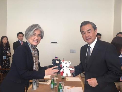 当地时间9月20日,在美国纽约,韩国外交部长官康京和(左)和中国外交部长王毅举行会谈并手持平昌冬奥吉祥物合影。(韩联社)