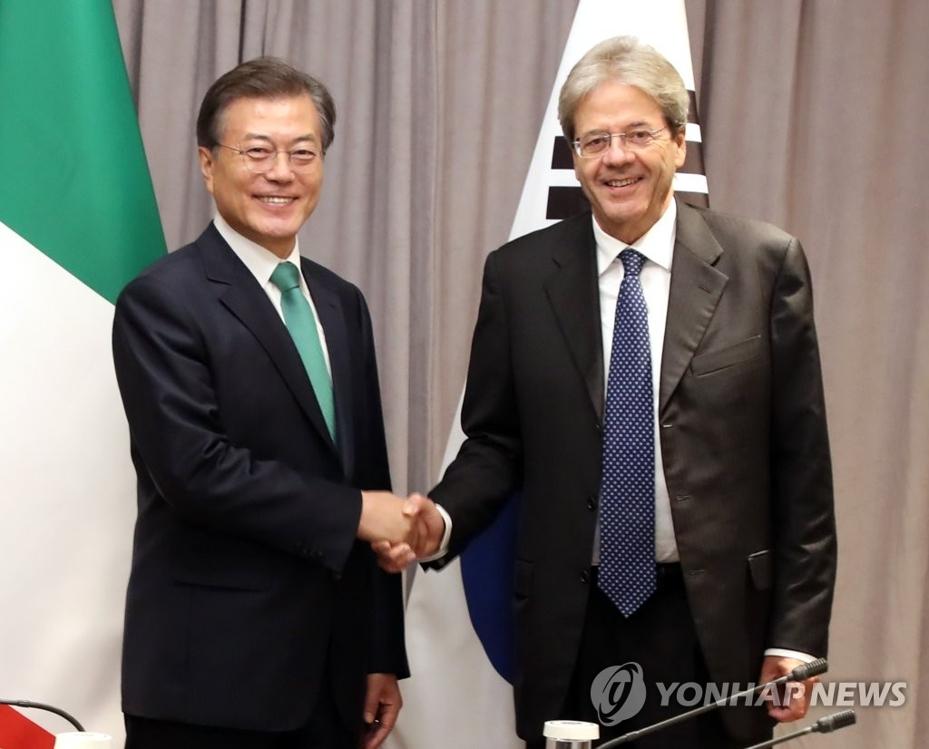 当地时间9月20日下午,在美国纽约巴克莱洲际酒店,韩国总统文在寅(左)和意大利总理保罗·真蒂洛尼握手合影。(韩联社)